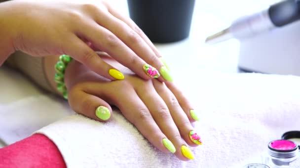 Detailní záběr kosmetička použití nehty na ženské hřebík salon hřebík. Detailní záběr ruky žena s žlutý lak na nehty po na manikúru