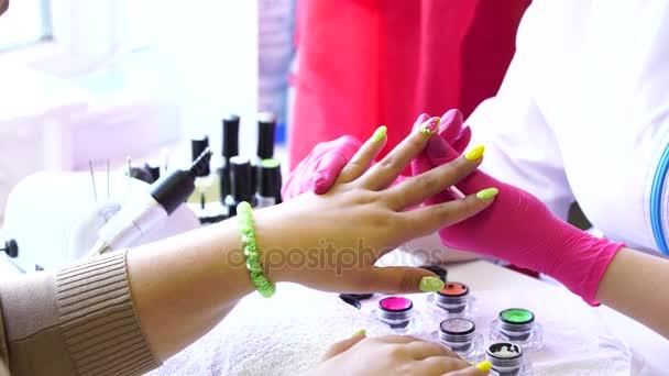 Detailní záběr kosmetička použití nehty na ženské hřebík salon hřebík. Detailní záběr ruky žena s žlutý lak na nehty po na manikúru.