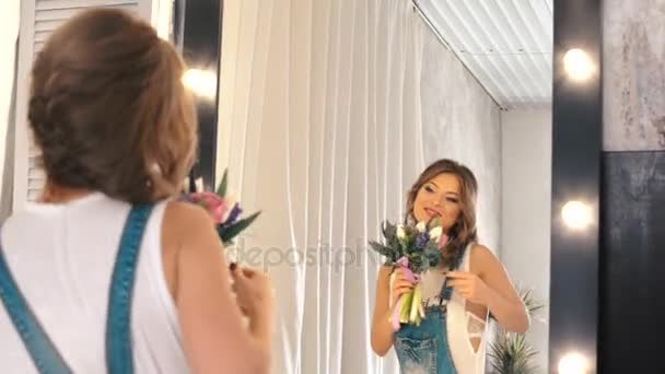 Beautiful young girl with a bouquet of flowers in jeans looks at himself in the mirror