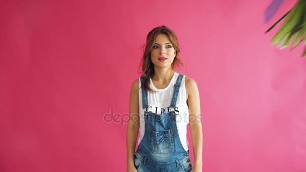 krásná žena s modré oči, blond vlasy, džíny, stojící na růžovém pozadí. Prezentovány s kyticí