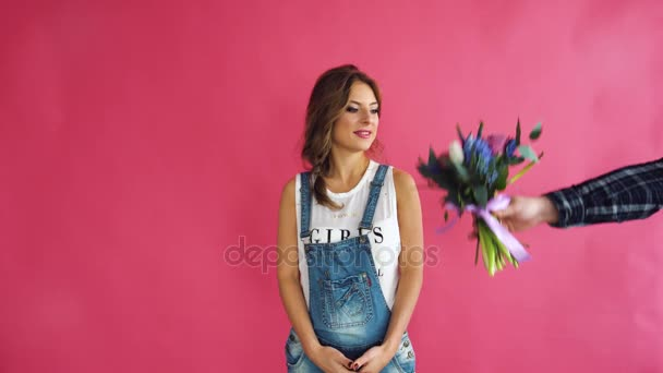 beautiful woman with blue eyes, blond hair, jeans, standing on a pink background. Presented with a bouquet of flowers
