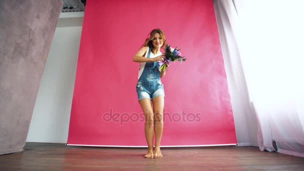Nice young blonde with blue eyes and a healthy long blond hair smelling flowers on a pink background in jeans