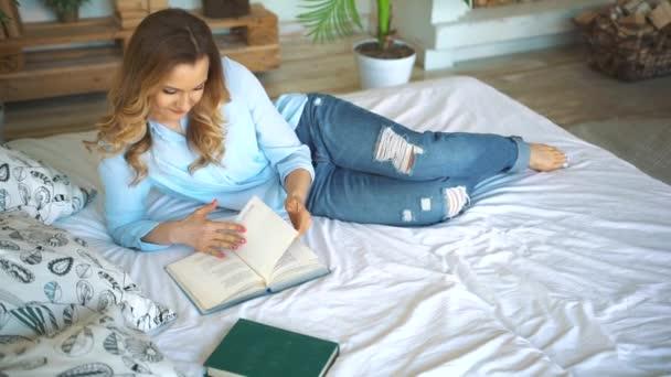 odpočinek, pohodlí, volný čas a lidé koncept - detail knihy čtení šťastná mladá žena v posteli doma ložnice