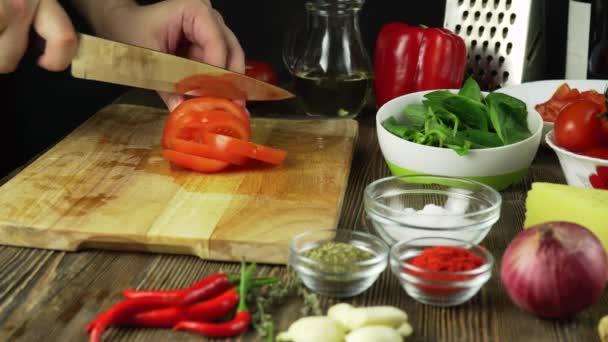 Messer schneidet Tomate auf Holzbrett