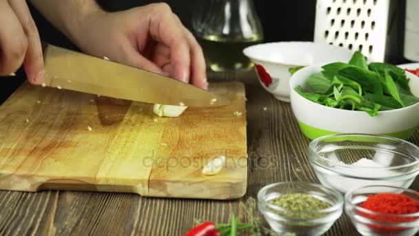 Šéfkuchař plátky česnek. Nůž, prkénko, česnek. Rychlé řezání zeleniny. Česnek. Česnek pro smažení. Rukou kuchaře.
