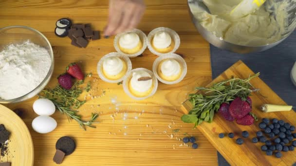 Modern desserts and cakes in the rustic style. Cupcakes with cream filling. Confectionery in the window. Professional pastry. Beautiful cake for a holiday in a blur. Cupcakes in hand.