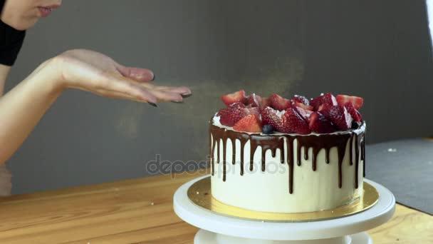 Díszítő eper torta a séf kezében