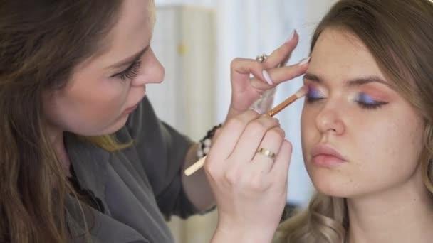 A mester egy make-up kijelző szépségszalon modell készül. A sminkes szakmai csinál egy smink.