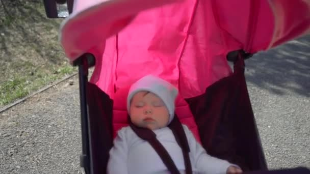 sladký malý chlapeček spí v kočárku