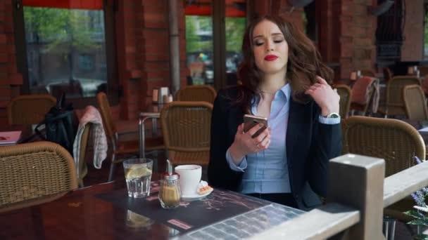 Atraktivní podnikatelka obleku pomocí Smartphone v venkovní kavárna, pití kávy. Zpomalený pohyb. Profesionální obchodní žena mluví, komunikace na mobil venku. Život ve městě Business