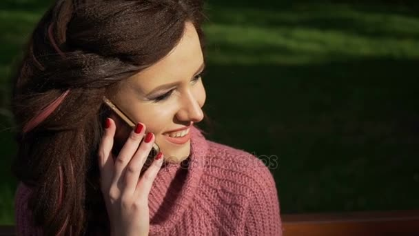 Gimbal shot of female teen girl talking on the phone sitting on bank in spring sunny day, uhd prores footage