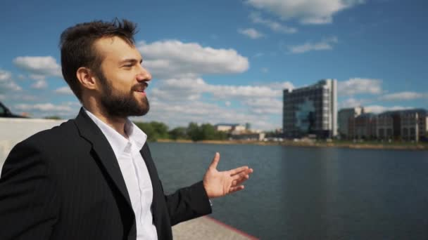 young handsome man with full-beard hipster talks to camera - city in background