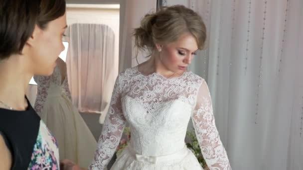 190c8d0bf0dd Konzultant pomohl budoucí nevěsta si vybrat svatební šaty– stock záběr