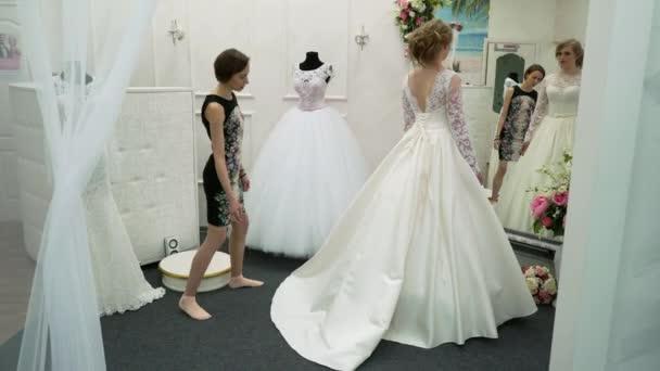 Junge Frau Wahlt Eine Brautkleid Im Brautmodengeschaft Stockvideo