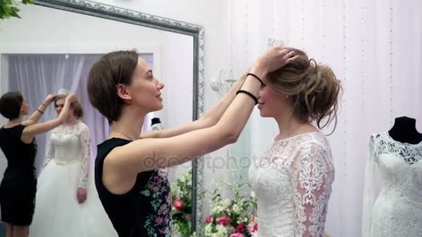 0d779286c490 Παράνυμφος βοήθησε η μέλλουσα νύφη να επιλέξει το νυφικό. Νεαρή γυναίκα  προετοιμασία για το γάμο– πλάνα αρχείου
