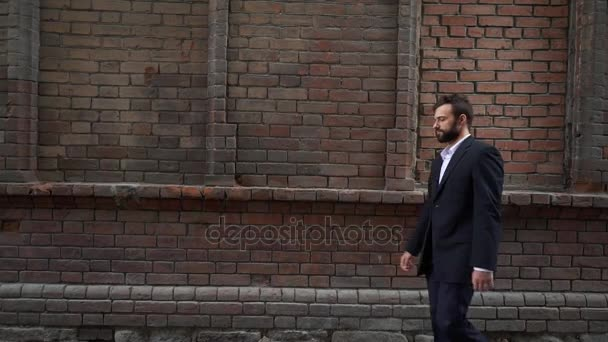 Handsome Young Male Guy Entrepreneur And Student Hurry On Business Meeting Returns From Lunch Going Home After Work Looks At His Watch Put On By On Hand Late And Goes On Background Of Brick Wall