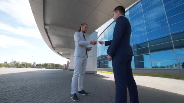 Two business man exchanging business cards and talking