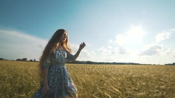 A cute young girl walks by herself in a golden field of wheat