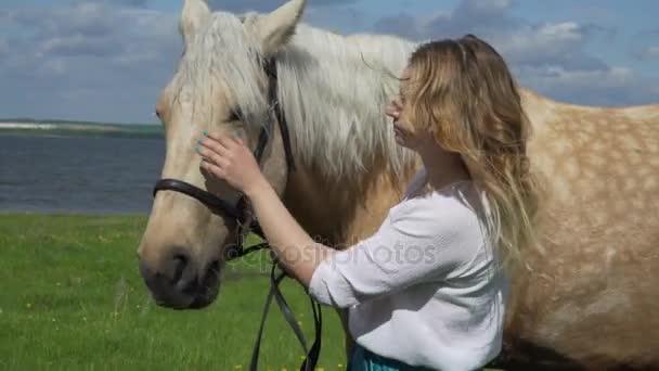 Dívka hladí na bílém koni na ranči za slunečného dne