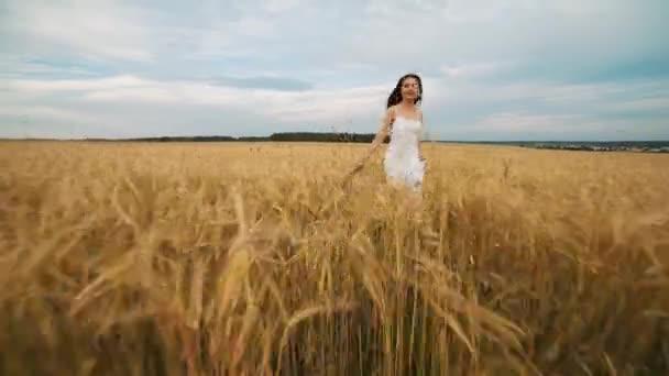 Krásy dívka venku těší přírody. Krásná dívka dospívající Model v bílých šatech, na jaře pole, sluneční světlo. Záře slunce zdarma šťastná žena. Posílený v teplých barvách