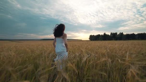 Szépség lány a szabadban élvezi természet. Gyönyörű tizenéves lány fut a tavaszi mezőn, nap fény fehér ruhában. Ragyogás növekvõ ingyenes boldog nő. A meleg színekkel tónusú