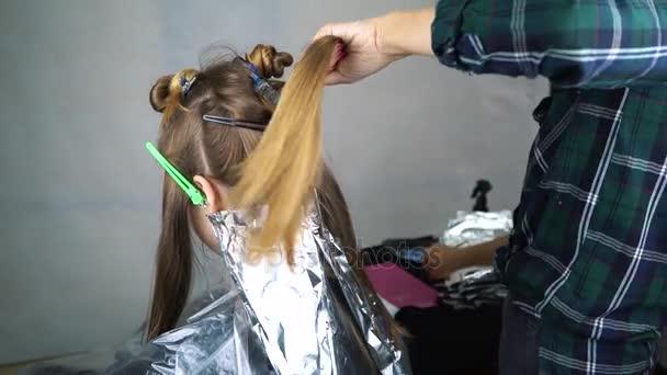 Kadeřník kadeřník dělá vlasy barvení, blonding. Ona používá štětec. Zavřít pohled. Kadeřníci ruce v černé rukavice. Holičství, kadeřnictví. Slunečního světla proudí windows. Slunečno