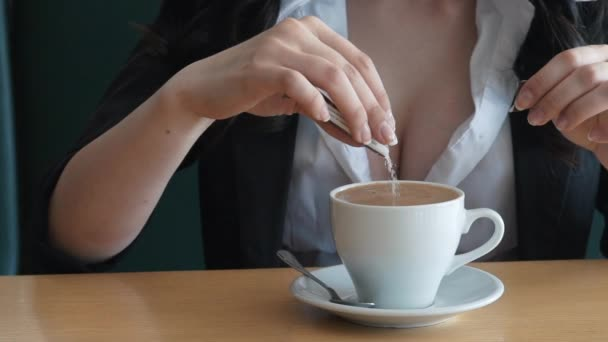 Close up footage of young Caucasian woman pouring sugar into a cup of espresso coffee.