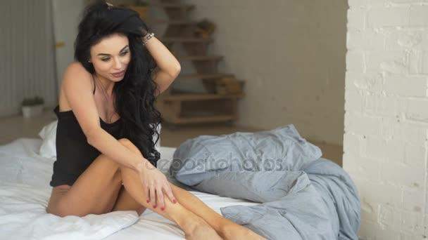 Foto smyslné krásná bruneta žena sedící na posteli, na sobě elegantní černé spodní prádlo