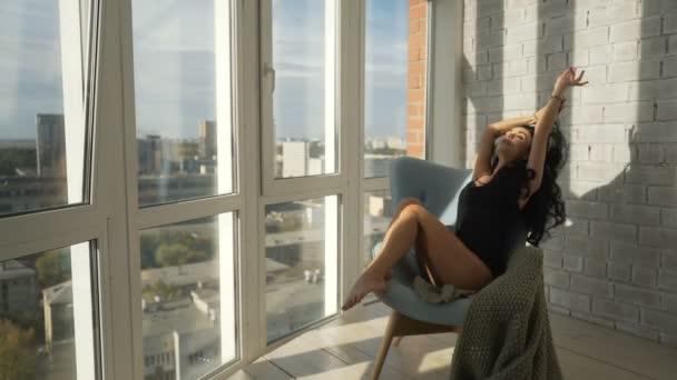 Krásná nahá dívka na sobě svetr sedí na posteli brzy ráno a objetí polštář. Flirtuje a pokusí se tě svést