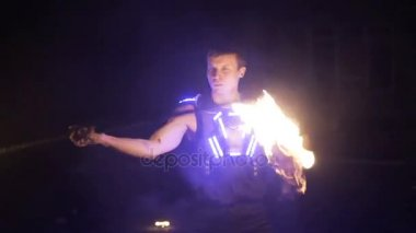 Fire show. Handsome male fire performer twirling fire baton with several wicks.