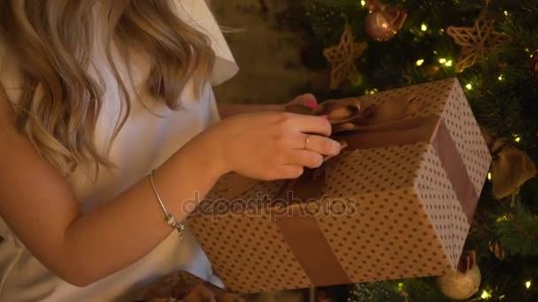 dívka balení dárkové krabice poblíž vánoční stromeček doma