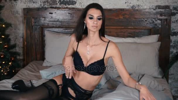 Mädchen in erotische schwarze Unterwäsche auf einem Bett liegt und sexuell vor der Kamera posiert. Slow-Motion. Close-up