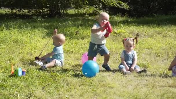 Gruppe fröhlicher Kinder, die draußen im Sommerpark spielen. Mütter kümmern sich um ihre Kinder, die im Gras sitzen.