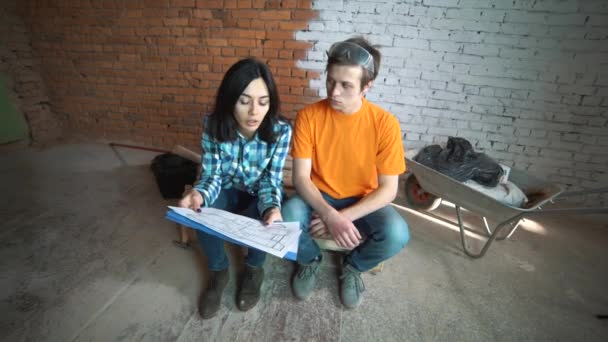 The customer sends the plan of the house to the Builder, explains how to redevelop the house. A man and a woman are watching their house plan.
