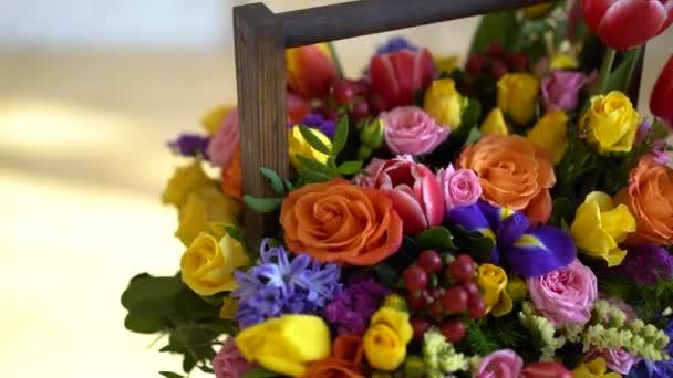 košík květin, světlé barvy, růže a tulipány.