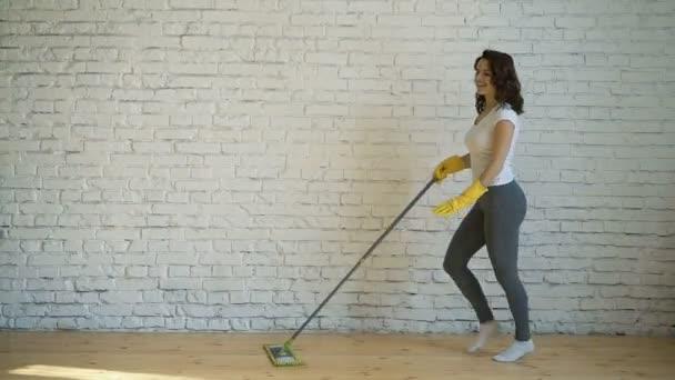eine tanzende junge Frau, die eine Frau in gelben Handschuhen putzt, lacht, hält einen Wischmopp in der Hand