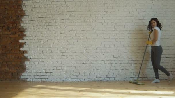 Žena, čištění parkety v obývacím pokoji. Detail