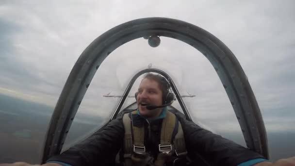 Usmíval se, pilot sedí v kokpitu světle akrobatických letadel, emoce z letu, letecká akrobacie