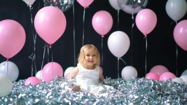 Šťastná dívka v bílých šatech šumivé slaví s rukou a úsměv nebo křičí radostí při chytání konfety zároveň baví