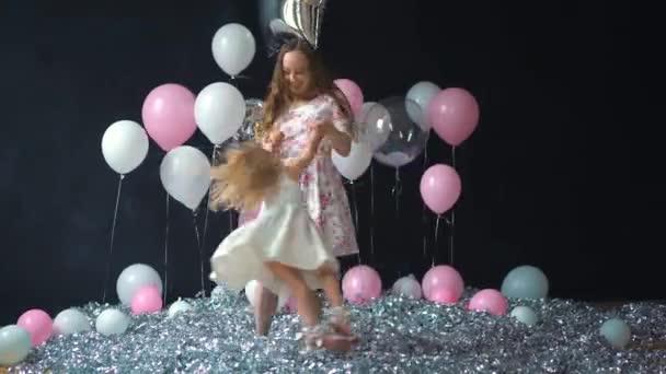 Portrét mladé matky a dcery baví a pózování s barevnými helium balónky