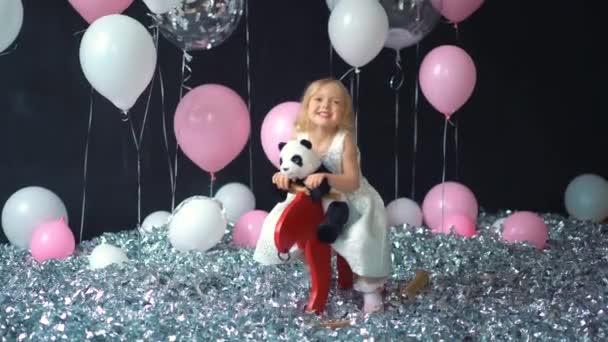 Děti si hrají v místnosti. Děti na koni, houpací hračka. Malá holčička hraje v mateřské škole nebo školce. Krásné miminko pro miminko a batole. Hračky pro předškoláky. Roztomilé dítě baví doma.