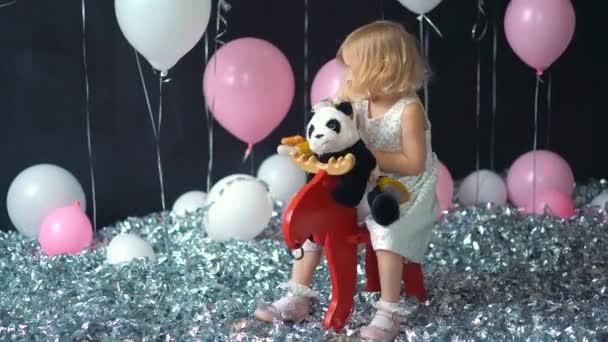 Děti si hrají v místnosti. Děti na koni, houpací hračka. Malá holčička hraje v mateřské škole nebo školce. Krásné miminko pro miminko a batole. Hračky pro předškoláky. Roztomilé dítě baví doma