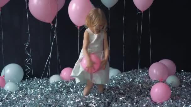 Portrét krásné holčičky usměje a drží v ruce barva bublinu ve studiu s mnoha balónky a sladkosti hračkářství.