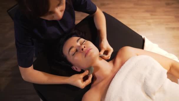 Lázně žena obličejové masáže. Masáž obličeje ve spa salonu krásy. Žena se těší relaxační masáž obličeje v kosmetologii lázeňském centru. Péče o tělo, kosmetika, wellness, kosmetické ošetření.