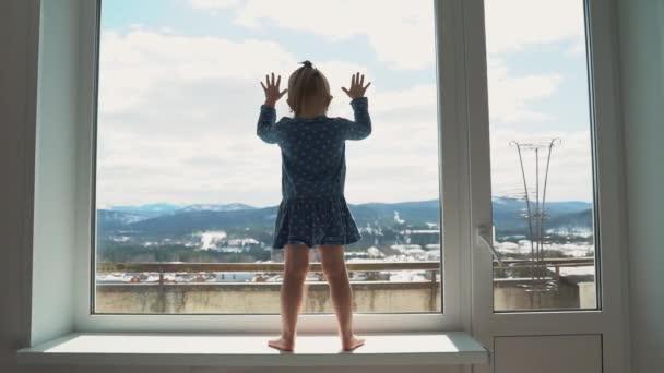 Dítě je doma v izolaci za oknem, pláče a chce si hrát venku. Malá holka udeří rukou do skla..