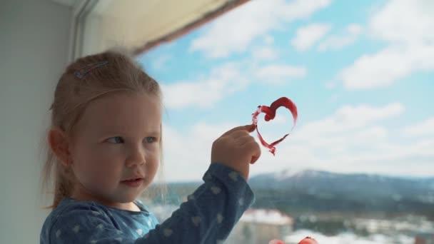 Egy kislány szívet rajzol az ablakra az ujjával..