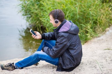 Young man spirits sits on the river bank with a phone and listens to music