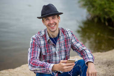Young smiling man in fashionable clothes with a phone listens to music