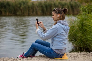Young smiling woman in excellent spirits with a phone listens to music