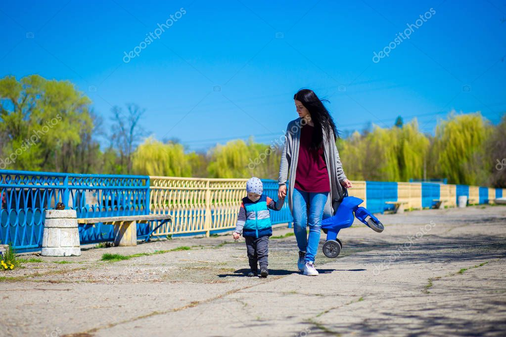 Young mother walks with small son outdoors with children's motorbike. Active childhood